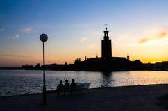 Silhouet van vrouwen die op bank, het Stadhuis van Stockholm, Zweed zitten stock afbeeldingen