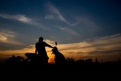 Silhouet van vrouwen die op een motorfiets zitten Royalty-vrije Stock Foto's