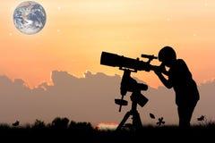 Silhouet van weinig jongen die door een telescoop kijken Royalty-vrije Stock Afbeeldingen