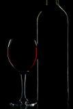 Silhouet van wijnfles en glas over zwarte Stock Foto