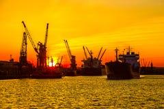 Silhouet van zeehavenkranen over zonsondergang Stock Foto's
