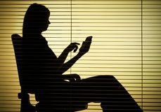 Silhouet van zittingsvrouw met (blinde) calculator stock afbeelding
