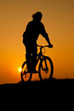 Silhouet of a young adult riding a bike. At sunset Stock Images