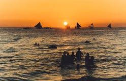 Silhouet in zeewater bij zonsondergang stock fotografie