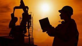 Silhouetarbeider en oliepomp stock video