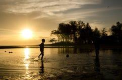Silhouetbeeld een voetbal van het jongens speelstrand over zonsopgangachtergrond royalty-vrije stock foto