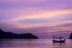 Silhouetboten en berg in het overzees met bac van de pupleschemering Stock Foto