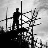 Silhouetbouwvakker op steigerbouwterrein Stock Foto's