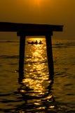 Silhouetbrug en een boot in zonsondergang Royalty-vrije Stock Afbeeldingen