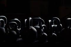 Silhouetdomoor voor gewichtheffen in gymnastiek Zwarte kettlebells 24kg weightlifting Royalty-vrije Stock Fotografie