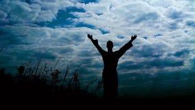 Silhouete del hombre se coloca en la roca de piedra con los brazos aumentados en día ventoso lentamente metrajes