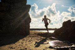 Silhouete female runner at beach. Young Aisan Healthy fitness woman running on sandy beach with natural stone arch at sunrise in Rayong, Thailand. Silhouette Stock Photo