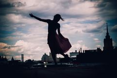 Silhouete of girl in dress standing on the background of skyline royalty free stock photo