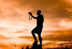 Silhouetfotograaf die foto's in de zonsondergang van de aardmening nemen Stock Afbeeldingen