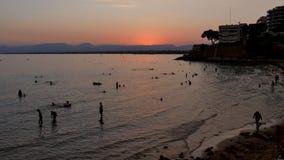 Silhouetgroep die reizigersvreugde en op strandkust in zonsondergangtijd reraxing springen, de Openluchtmensen van het activiteit stock video