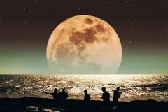Silhouetgroep mensen op het strand bij nacht, met super volle maan met sterren op de hemel het landschap van de sprookjefantasie Stock Afbeeldingen