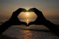 Silhouethart gevormde handen die op vage zonsondergang over het strand gesturing Royalty-vrije Stock Foto's