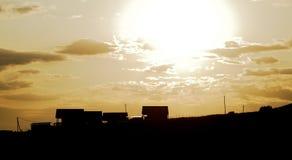 Silhouethuizen met bruine hemel en zon Royalty-vrije Stock Foto