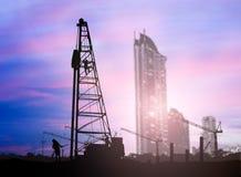 Silhouetingenieur in een bouwterrein over Vage constructio Stock Afbeelding