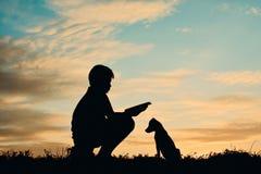 Silhouetjongen die een boek met weinig hond lezen royalty-vrije stock fotografie