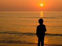 Silhouetjongen die zich op het strand bevinden Stock Afbeeldingen