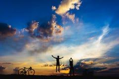 Silhouetjongens die op zonsondergang springen royalty-vrije stock fotografie