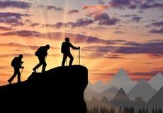Silhouetklimmers die tot bovenkant van berg stijgen royalty-vrije stock afbeelding