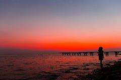 Silhouetmeisjes bij zonsondergang dichtbij het overzees royalty-vrije stock foto