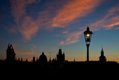 Silhouetmening van Charles Bridge en stad van Praag bij dageraad Royalty-vrije Stock Foto's