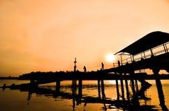 Silhouetmens die bij pier vissen Royalty-vrije Stock Foto's