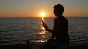 Silhouetmens met digitale tablet in handen bij zonsondergangstrand De zon is bijna plaatste achter de oceaan stock videobeelden