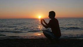 Silhouetmens met digitale tablet in handen bij zonsondergangstrand De zon is bijna plaatste achter de oceaan stock video