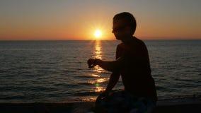 Silhouetmens met smartwatch op hand bij zonsondergangstrand Hij raakt de slimme horloges en controleert het bericht De zon is stock videobeelden