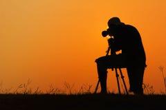 Silhouetmensen die van fotograaf foto voor een zonsopgang schieten Stock Foto