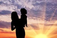 Silhouetmoeder met een baby Royalty-vrije Stock Afbeeldingen