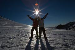 Silhouetpaar met handen die op sneeuw tegen zon en blauwe hemel worden opgeheven Stock Afbeelding