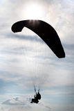 Silhouetparachutisten achter elkaar in de hemel Stock Foto's