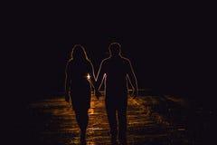 Silhouetparen in de koplampen Lawaai, korrel gestileerd beeld stock fotografie