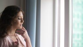 Silhouetportret van mooi meisje dat duidelijk uitkomt en het venster kijkt stock video