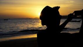 Silhouetrug van jonge mannelijke reis backpacker met hoed die foto's van het landschap van het de zomerstrand neemt tegen zonsond stock videobeelden