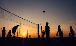 Silhouets of men playing beach volleyball at the evening glory time Royalty Free Stock Image