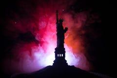 Silhouetstandbeeld van vrijheid op donkere gestemde mistige achtergrond Standbeeld van Vrijheid op de achtergrond van kleurrijke  royalty-vrije stock foto