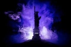 Silhouetstandbeeld van vrijheid op donkere gestemde mistige achtergrond Standbeeld van Vrijheid op de achtergrond van kleurrijke  stock afbeelding