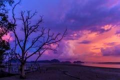 A silhouetté la plage au temps de coucher du soleil, sur le ciel crépusculaire ensuite Image stock