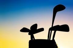 Silhouett do equipamento de golfe, clubes no por do sol Fotografia de Stock