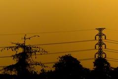Silhouette à haute tension de poteau électrique et temps de soirée Photos libres de droits