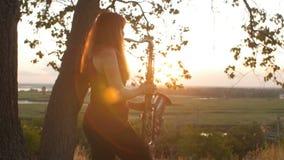 Silhouette à la jeune belle fille rousse de coucher du soleil jouant la nature de saxophoneon, une femme soufflant dans le tuyau, clips vidéos
