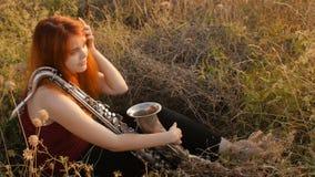 Silhouette à la jeune belle fille rousse de coucher du soleil jouant la nature de saxophoneon, une femme soufflant dans le tuyau, banque de vidéos
