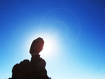 Silhouette équilibrée de roche dans Sun Image libre de droits