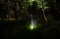 Silhouette étrange dans une forêt fantasmagorique foncée la nuit, lumières surréalistes de paysage mystique avec l'homme rampant photo stock